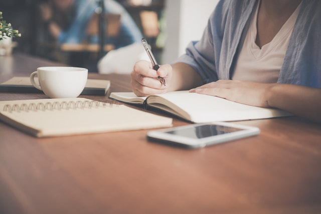 woman studying a desk with coffee while in her LSAT accountability group